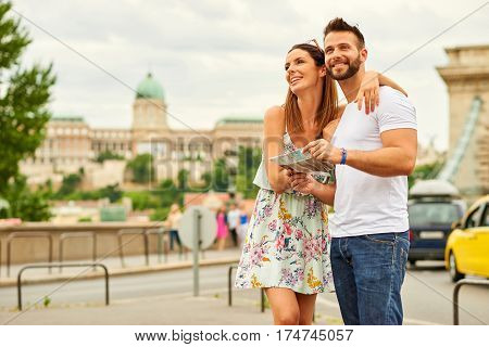 A beautiful young tourist couple are standing and looking around with the castle of Buda and the Chain Bridge behind them in Budapest, Hungary.