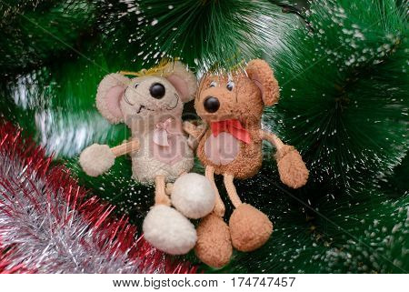 Two funny toy mouse sitting on a Christmas tree arm in arm