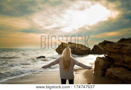 Woman In Sweater On Winter Beach At Sunset.