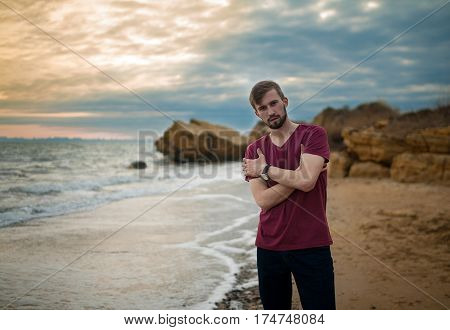 Guy in tee-shirt on winter beach at sunset. Clouds at sunset sky background and rocks are visible from behind.