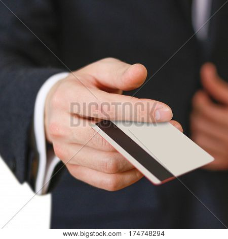 Businessmen Holding Credit Card Proposing It To You. Hand In Black Suit Holds Out A Blank Grey Credi
