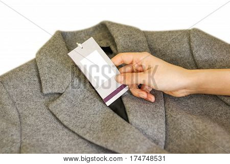 Close Up Of Hand Holding Price Tag Of Grey Wool Coat. Clothes, Wear And Fashion Concept.