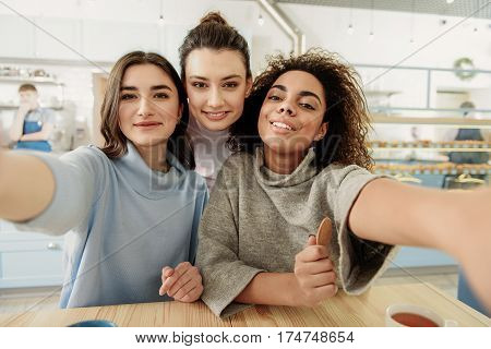 Hilarious young women are making selfie in cafe. They looking at camera with bright smile while stretching hands