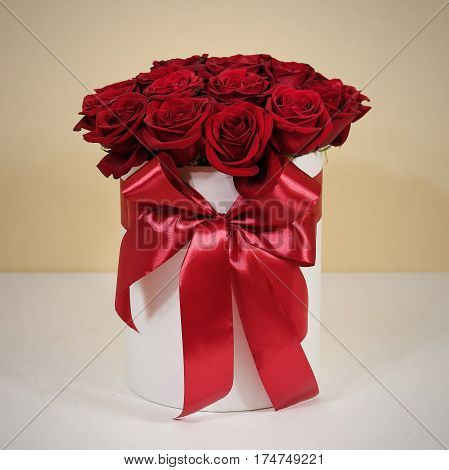 Rich gift bouquet of 21 red roses. Composition of flowers in a white hatbox. Tied with wide red ribbon and bow.