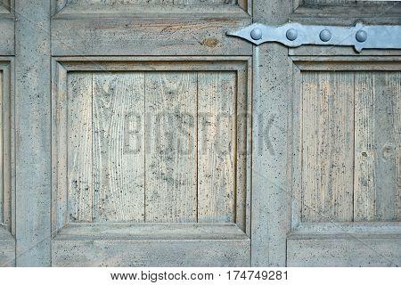 Old door hinge on old blue wooden door with weathered paint