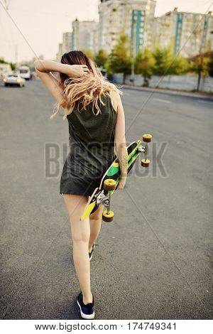 Beautiful young tattooed woman with his longboard on the road in the city in sunny weather