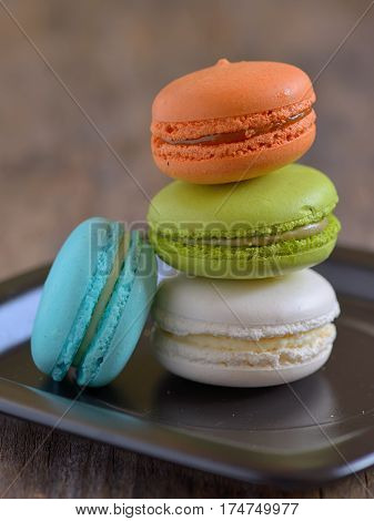 french colorful macarons on wooden table, close up