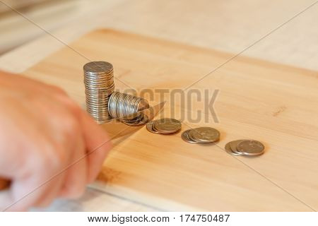 Hand With A Knife Cutting A Pile Of Coin. Concept Of Budget Cuts, Savings, Recession. The Division I