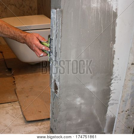 Man's Hand With Spatula In The Repair Room. Plasterer Worker Aligns Wall Plaster Or Lime