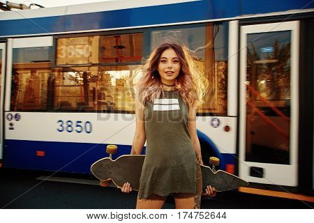 Beautiful young woman with his longboard on the road in the city in sunny weather. Bus passes in the background