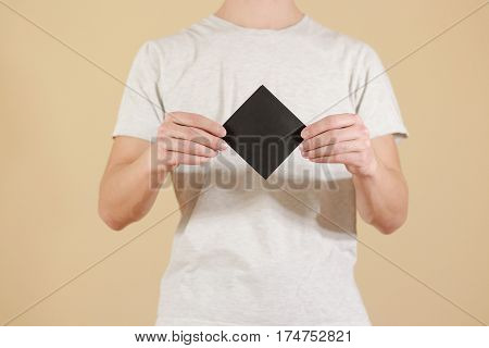 Man Showing Blank Black Square Flyer Brochure Booklet. Leaflet Presentation. Pamphlet Hold Hands. Ma