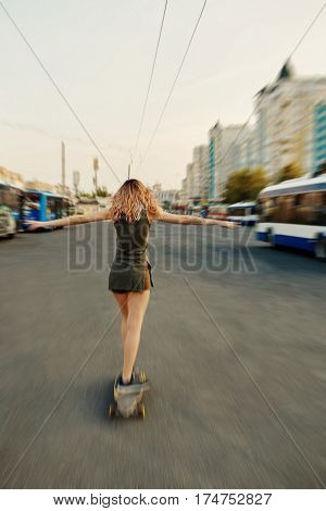 Beautiful young girl with tattoos riding on her longboard on the road in the city in sunny weather. Extreme sports. Rear view of motion