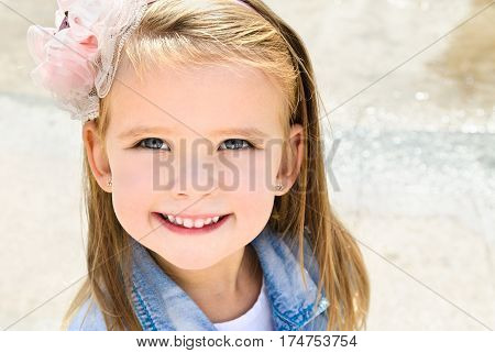 Outdoor portrait of cute little girl in spring day