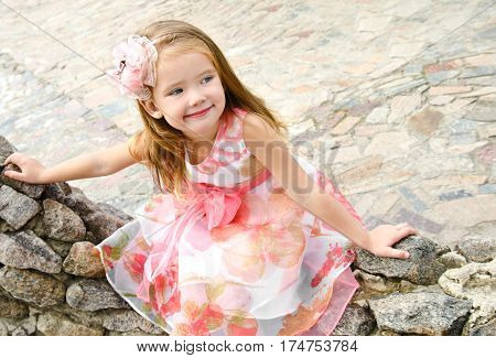 Portrait of cute little girl in princess dress sitting on the stones outdoor