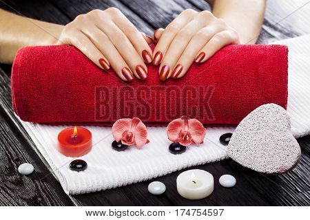 beautiful red manicure with candles, red orchid flower and towel on the black wooden table.