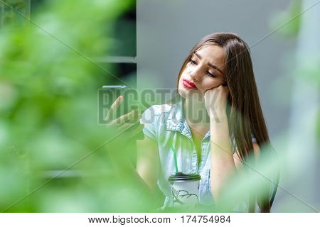 Sad young woman with long hair looking at smartphone in outdoor cafe