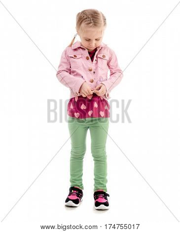 Adorable child trying to zip her pink coat, wearing green pants, isolated on white background