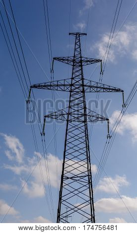 Electricity transmission tower power supply pylon with a blue sky background.
