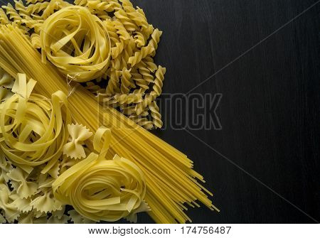 A variety of types and forms of dry Italian pasta. the view from the top on a black background. Space to the right