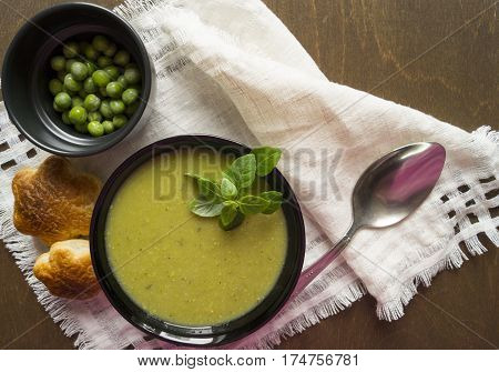 cream soup of green peas in a black bowl