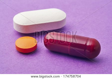 Pills over a purple background. Medicament treatment. Health care photo