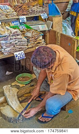 The seller cuts the dried fish into the small cubes at his stall in Fose Market Pettah Colombo Sri Lanka.