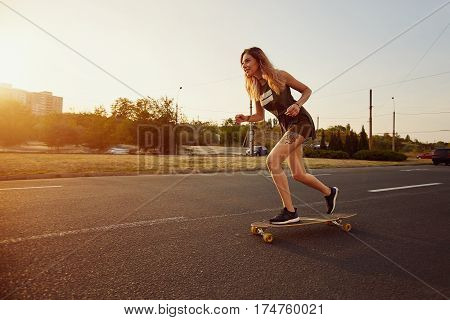 Beautiful young girl with tattoos riding on his longboard on the road in the city in sunny weather. Extreme sports