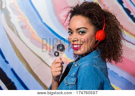 Outgoing woman with bright makeup hearing song through headset while keeping audiotape in arm. Copy space