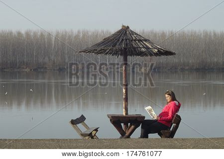 Beautiful young woman rests by the river Danube in Serbia and reads magazine