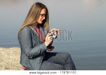 Young woman with vintage retro film camera adjusts the camera and takes photos on the bank of  the Danube river in Serbia.