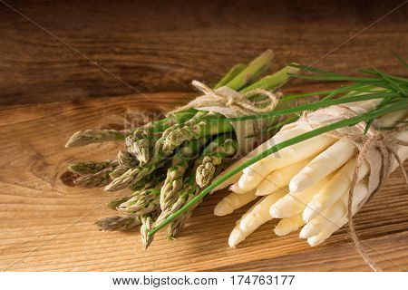 Fresh green and white asparagus with a bunch of chives on a wooden board
