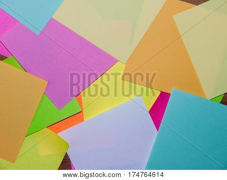 A close up image of a pile of Post It notes in various colours