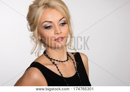 Beautiful blond woman with fashion hairstyle on a gray background