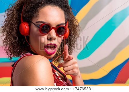 cheerful young woman flourishing arm while performing song and listening it through earphones. Copy space on colorful wall