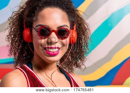 Portrait of Happy female with blue eye look wearing sunglasses and hearing song thorough headset. Copy space