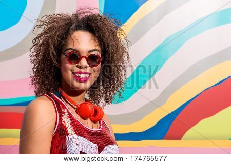 retro colorful background. outgoing african woman with curly hair wearing earphones and smiling. Copy space