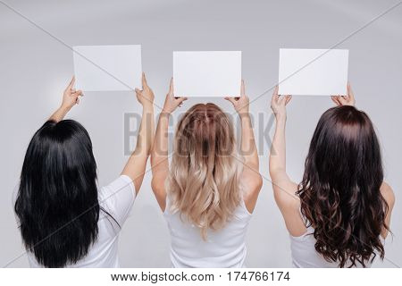 Looking to the future. Gorgeous elegant powerful standing with their hands being up in the air holding pieces of paper while turning their backs to the camera