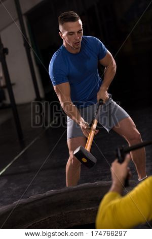 Sledgehammer Tire Hits young muscular man workout at gym with hammer and tractor tire