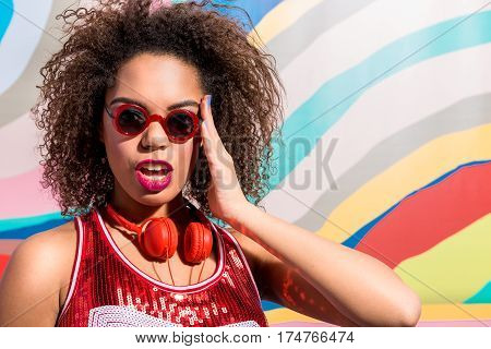 Portrait of Cheerful mulatto young woman with bright makeup and wearing earphones. Copy space