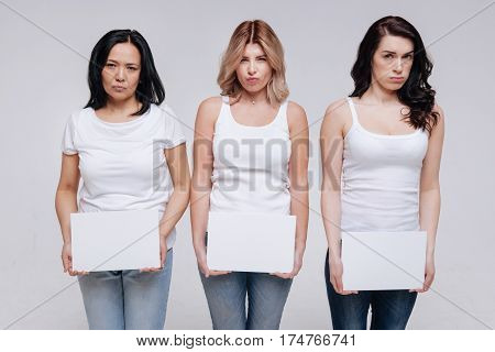 Little bit upset. Artistic pretty stunning ladies acting on set while holding white pieces of paper and standing close to each other