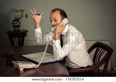 young business man gesturing aggressive and talking on the phone