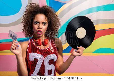 Waist up portrait of Surprising female with curly hair wearing earphones and keeping audiotape and phonograph record in her arms while standing near colourful picture
