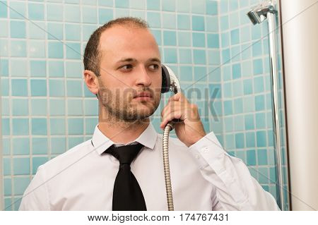 serious handsome business man standing in bathroom with shower in hand
