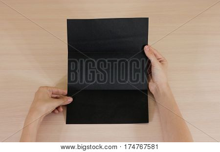 Hands Holding Blank Black Brochure Booklet In The Hand. Leaflet Presentation. Pamphlet Hand Man. Sho