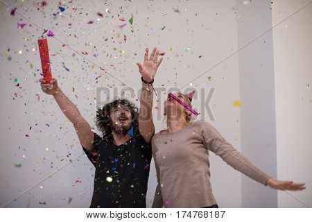 happy young romantic  couple in love  celebrating and blowing confetti decorations at new year and charismas  party