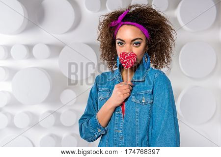 Calm african woman with blue eye look eating lollipop in the form of heart. Copy space