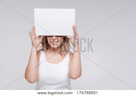 Just look at that smile. Magnetic emotional pretty woman holding a sheet of paper hiding her eyes while posing for a professional photographer
