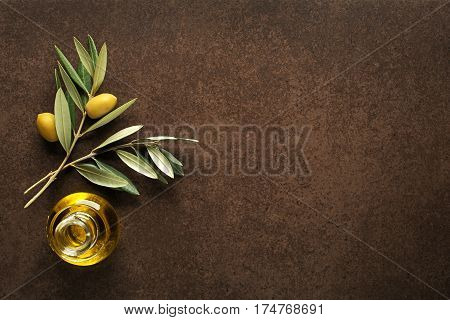 Olive oil and olive branch on brown table