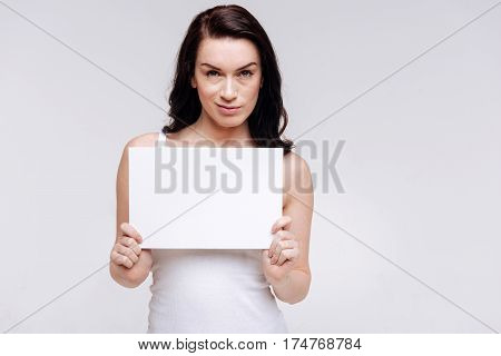 Not impressed. Devoted elegant contemporary woman posing with a piece of paper and showing required emotion while advertising social equality