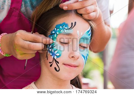 Child animator, artist's hand draws face art to little girl. Blue butterfly painting. Children birthday party entertainment